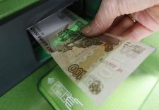 """Женщина забирает деньги из банкомата Сбербанка в Красноярске. 27 января 2015 года. Рубль дешевеет утром понедельника из-за сокращения продаж экспортной выручки в начале месяца, после понижения ключевой ставки ЦБР, на фоне увеличения внешней долговой нагрузки и угрозы новых западных санкций против России в феврале, а также в условиях """"мусорного"""" рейтинга S&P и рисков изменения до этого статуса рейтингов других агентств. REUTERS/Ilya Naymushin"""