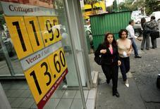 Unas personas pasan frente a una casa de cambios en Ciudad de México, oct 8 2008. Las remesas a México crecieron un 7.8 por ciento en 2014 a 23,607 millones de dólares, para consolidarse como una de las principales fuentes de divisas del país, mostraron el martes cifras del Banco de México (central).   REUTERS/Daniel Aguilar