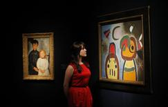 """A member of staff poses with """"L'oiseau au plumage deploye vole vers l'arbre argentee"""" (R) by Joan Miro at Christie's auction house in London, January 30, 2015.  REUTERS/Suzanne Plunkett"""