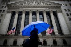 Женщина проходит мимо здания фондовой биржи в Нью-Йорке. 2 февраля 2015 года. Американские фондовые индексы S&P 500 и Nasdaq снизились в среду, завершив двухдневное ралли, за счет падения цен на нефть и новых опасений за еврозону в последние минуты торгов. REUTERS/Brendan McDermid