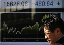 Мужчина у брокерской конторы в Токио. 16 января 2015 года. Азиатские фондовые рынки завершили торги вторника разнонаправленно под влиянием событий в Греции и отчета об инфляции в Китае. REUTERS/Toru Hanai