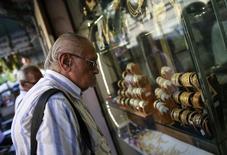 Мужчина рассматривает золотые браслеты на витрине ювелирного магазина в Мумбаи. 21 октября 2014 года. Цены на золото растут на фоне спада на фондовых рынках и опасений за будущее Греции в составе еврозоны. REUTERS/Danish Siddiqui