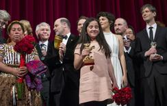 The niece (C) of Iranian film director Jafar Panahi appears on stage with jury members and prize winners after accepting the Golden Bear for Best Film on her uncle's behalf, during the awards ceremony at the 65th Berlinale International Film Festival in Berlin February 14, 2015. REUTERS/Hannibal Hanschke