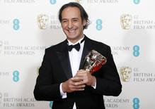 """Composer Alexandre Desplat celebrates after winning the award for best music for """"The Grand Budapest Hotel"""" at the British Academy of Film and Arts (BAFTA) awards ceremony at the Royal Opera House in London February 8, 2015.  REUTERS/Suzanne Plunkett/Files"""