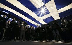 Protesters hold a giant Greek national flag during an anti-austerity and pro-government demonstration in front of the parliament in Athens February 15, 2015. REUTERS/Alkis Konstantinidis