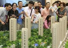 Personas observan un modelo de un complejo residencial en Hangzhou. Imagen de archivo, 17 agosto, 2014.  Los precios promedio de las viviendas nuevas en las 70 ciudades principales de China cayeron en enero por noveno mes consecutivo, pero mostraron algunas señales de estabilización en las ciudades más grandes, lo que sugiere una mejoría de la confianza en el mercado. REUTERS/Stringer