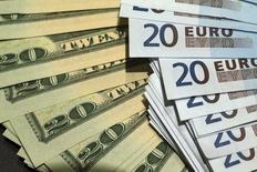 Банкноты по 20 долларов и 20 евро. Париж, 28 октября 2014 года. Курс доллара к евро и иене снижается после публикации протокола совещания ФРС, показавшего, что руководство центробанка не хотело бы повысить процентные ставки слишком рано. REUTERS/Philippe Wojazer