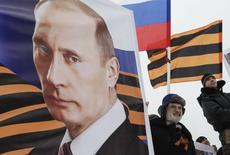 Человек держит в руках постер с изображением президент РФ Владимира Путина на митинге в Ставрополе 21 февраля 2015 года. Президент РФ Владимир Путин считает, что война между Россией и Украиной вряд ли возможна и надеется, что до нее никогда не дойдет. REUTERS/Eduard Korniyenko