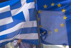 Grecia ha enviado en torno a medianoche una lista de reformas económicas a distintas instituciones europeas y al Fondo Monetario Internacional, dijo el martes una fuente cercana a la Comisión Europea. En la imagen, un hombre ajusta la bandera de Grecia (izq.) en las afureas de la embajada griega en Bruselas el 19 de febrero de 2015. REUTERS/Yves Herman