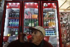 Una persona bebiendo una Coca-Cola en Ciudad de México, sep 9, 2013. La embotelladora mexicana Coca-Cola FEMSA (KOF), la mayor de la popular marca en el mundo, reportó el miércoles un alza del 0.3 por ciento en su utilidad neta del cuarto trimestre del 2014, en medio de débiles ventas en México y efectos por la conversión del tipo de cambio en Venezuela. REUTERS/Edgard Garrido