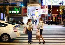 Women carry shopping bags in the Dotonbori amusement district of Osaka, western Japan November 19, 2014. REUTERS/Thomas Peter
