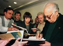 Turkish writer Yasar Kemal (R) gives autographs after a press conference at the 49th  Germany bookfair in Frankfurt October 18, 1997.  REUTERS/Files