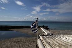 Una bandera griega flameando en una playa en Alimos, cerca de Atenas, mar 1 2015. Las posibilidades de que Grecia se retire de la zona euro en los próximos 12 meses son las más altas desde fines de 2012, aun después de la extensión del salvavidas financiero de Atenas, mostró el martes un sondeo realizado a inversores, con base principalmente en Alemania.  REUTERS/Alkis Konstantinidis