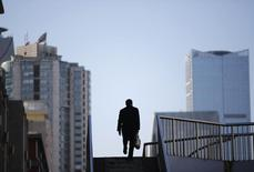 A man walking on a pedestrian bridge is silhouetted against skyscrapers in Beijing January 21, 2015. REUTERS/Kim Kyung-Hoon