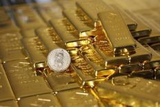 Слитки золота и монета в 1 швейцарский франк на заводе Oegussa в Вене. 7 ноября 2014 года. Цены на золото стабильны после двухдневного спада на фоне роста доллара до 11-летнего максимума. REUTERS/Leonhard Foeger