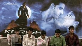 """Pedestrians sit in front of a poster of the upcoming Bollywood film """"Krrish"""" in Mumbai in this June 21, 2006 file photo.   REUTERS/Adeel Halim/Files"""