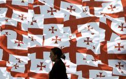 Женщина проходит мимо стены, на которой изображены флаги Грузии, в Тбилиси 24 мая 2010 года. Экономика Грузии может вырасти на 2 процента в 2015 году, но при этом существуют понижательные риски, сообщил глава миссии Международного валютного фонда в Грузии Марк Гриффитс в среду. REUTERS/David Mdzinarishvili