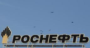 Логотип Роснефти на здании в Ставрополе 9 декабря 2014 года. Менеджмент Роснефти рекомендует снизить дивиденды за 2014 год на 36 процентов до 8,2 рубля на акцию, сообщила компания в презентации. REUTERS/Eduard Korniyenko