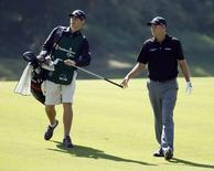 Bill Haas (R) of the U.S. gives his club to his brother and caddie Jay Haas Jr. after hitting from the seventh fairway during the final round of the Northern Trust Open golf tournament at Riviera Country Club in Los Angeles February 17, 2013. REUTERS/Danny Moloshok