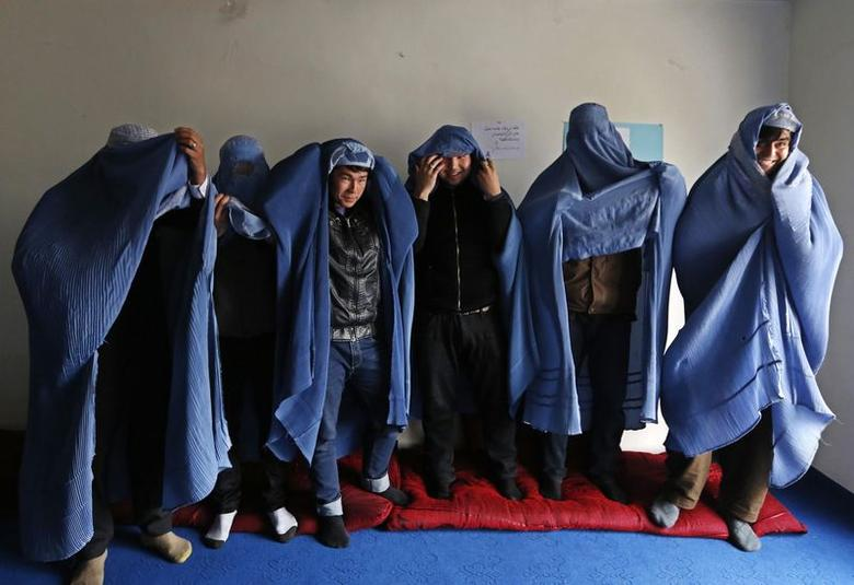 Male Afghan women's rights activist pose for media as they wear burqas to show their solidarity to Afghan women ahead of International Women's Day in Kabul March 5, 2015.   REUTERS/Mohammad Ismail