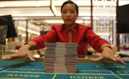 A Solaire Casino-Resort dealer practices her card skills on a baccarat table a few days before the casino's opening in Pasay city, Metro Manila in this March 14, 2013 file photo. REUTERS/Erik De Castro/Files