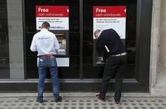 Unas personas utilizando un cajero automático del banco HSBC en Londres, mar 13 2014. Los bancos de Europa deben recortar sus gastos en un quinto y a la vez aumentar sus ingresos en un 15 por ciento para obtener una rentabilidad que esté en línea con sus niveles de costos de capital, indicó el lunes un estudio.  REUTERS/Suzanne Plunkett