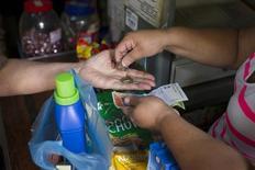 Credit Suisse bajó su previsión de crecimiento para América Latina en 2015 a un 1,3 por ciento desde un 2,2 por ciento, con recortes de pronósticos para seis de los ocho países de la región analizados en su informe trimestral, conocido el lunes. En la imagen de archivo, una persona compra mercadería en un supermercado en Caracas. 14 febrero 2013. REUTERS/Carlos Garcia Rawlins