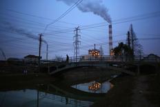 En la imagen, un hombre camina sobre un puente frente a unas chimeneas de una planta energética en Shanghai, el 23 de febrero de 2015. Pekín reducirá el consumo de carbón en cuatro millones de toneladas este año, dijo el vicealcalde de la capital china, Li Shixiang, como parte del plan para ponerle freno a los altos niveles de contaminación de la urbe. REUTERS/Carlos Barria