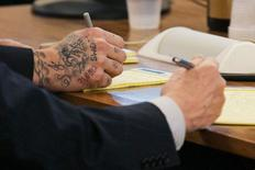 The hands of former NFL player Aaron Hernandez (L) and his attorney are seen during his murder trial at the Bristol County Superior Court in Fall River, Massachusetts March 11,  2015. REUTERS/Dominick Reuter/Pool