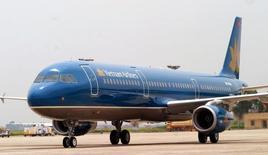 Самолет Vietnam Airlines в аэропорту Ханоя. 7 июля 2004 года. Вьетнамский национальный перевозчик Vietnam Airlines Co пройдет листинг акций на фондовой бирже в стране к ноябрю этого года, сказал исполнительный директор компании Фам Нгок Мин. REUTERS/Kham  KHAM/LA