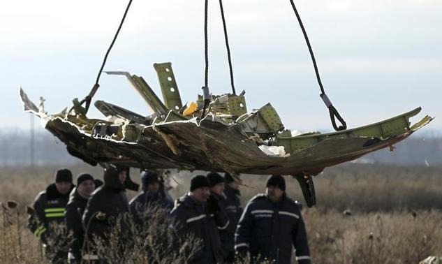 7d2756f84d608 A crane transports a piece of the Malaysia Airlines flight MH17 wreckage at  the site of