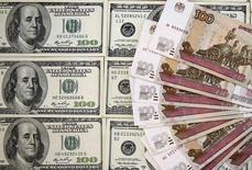 Банкноты российского рубля и доллара США. Сараево, 9 марта 2015 года. Рубль в понедельник торгуется с незначительными изменениями вокруг уровней пятничного закрытия, реагируя в основном на изменения баланса сил покупателей и продавцов валюты в условиях подешевевшей нефти и начавшегося сегодня налогового периода. REUTERS/Dado Ruvic