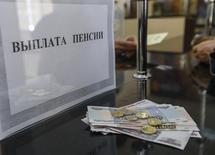 Окошко для выплаты пенсий в почтовом отделении в Симферополе. 25 марта 2014 года. Российские власти могут конфисковать более 3 триллионов рублей пенсионных отчислений граждан, если в споре о будущем обязательной накопительной пенсионной системы в ближайшие дни победят сторонники её слома, опасаются бывшие и нынешние чиновники. REUTERS/Shamil Zhumatov