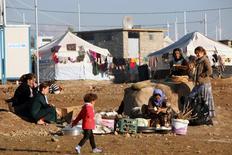 Membres de la minorité religieuse kurdophone yazidie dans un camp de déplacés dans la province irakienne de Dohuk. Le bureau du Haut-Commissariat des Nations unies aux droits de l'homme de l'Onu estime que les combattants de l'Etat islamique ont commis un génocide contre la minorité irakienne yazidie ainsi que des crimes contre l'humanité et des crimes de guerre visant des civils et des enfants en Irak. /Photo prise le 29 novembre 2014/REUTERS/Ari Jalal