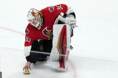 Mar 15, 2015; Ottawa, Ontario, CAN; Ottawa Senators goalie Andrew Hammond (30) picks up a hamburger that was thrown on the ice at the end of game against the Philadelphia Flyers. The Senators defeated the Flyers 2-1 in a shoot-out at the Canadian Tire Centre. Mandatory Credit: Marc DesRosiers-USA TODAY Sports