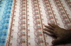 Plantillas de 100 y 10 reales en la Casa de la Moneda de Río de Janeiro, ago 23 2012. El real brasileño cayó el jueves a un mínimo de casi 12 años porque los conflictos políticas alentaban el temor de los inversores por el futuro de una propuesta de reforma fiscal en la mayor economía de América Latina. REUTERS/Sergio Moraes