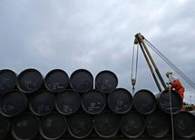 A worker prepares to transport oil pipelines to be laid for the Pengerang Gas Pipeline Project at an area 40km (24 miles) away from the Pengerang Integrated Petroleum Complex in Pengerang, Johor, February 4, 2015. REUTERS/Edgar Su