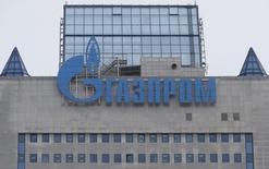 Логотип Газпрома на штаб-квартире компании в Москве 24 февраля 2015 года. Газпром обещает выплатить дивиденды за 2014 год после погашения Украиной части долга за газ, сказал финдиректор концерна Андрей Круглов журналистам в пятницу. REUTERS/Maxim Zmeyev