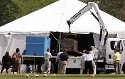 Friends and family watch as members of the FBI evidence response team exhumes the body of Emmett Till at Burr Oak Cemetery in Alsip, Illinois, in this file photo taken June 1, 2005. REUTERS/Frank Polich/Files