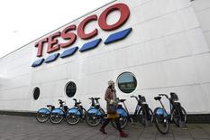 A woman walks past a Tesco supermarket in central London, December 9, 2014.   REUTERS/Toby Melville