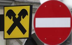 A Raiffeisen Bank International logo is pictured next to a traffic sign in Vienna January 16, 2015. Ukraine's descent into chaos, Russia's economic crisis, political turmoil in Hungary and sluggish Romanian growth caught Austrian banks out after years of profit and led to a series of profit warnings, exposing risk management failings and a culture of hoping for the best. Raiffeisen Bank International said this month all its businesses were under review and it will decide by mid-2015 whether to exit a market or two.  REUTERS/Heinz-Peter Bader (AUSTRIA  - Tags: BUSINESS LOGO)