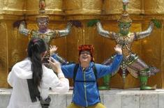 A Chinese tourist strikes a similar pose to statues as they visit the Grand Palace in Bangkok March 23, 2015. REUTERS/Chaiwat Subprasom