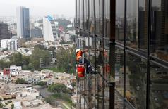 Un trabajador limpiando los ventanales de las oficinas de Petroperú en Lima, mayo 28 2012. La estatal Petroperú rechazó su opción de tener el 25 por ciento de participación en la explotación de dos bloques petroleros con la firma Graña y Montero, cancelando un plan previo de volver a producir crudo por primera vez en más de dos décadas. REUTERS/Mariana Bazo
