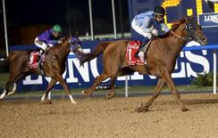 William Buick (R), riding Prince Bishop, races to the finish line to win the ninth and final race of the Dubai World Cup at the Meydan Racecourse in Dubai March 28, 2015. REUTERS/Ahmed Jadallah