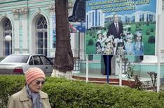 Женщина проходит мимо предвыборного плаката Ислама Каримова в Ташкенте. 29 марта 2015 года. Узбекский политический долгожитель Ислам Каримов в понедельник был провозглашен победителем воскресных президентских выборов, которые Организация по безопасности и сотрудничеству в Европе сочла в очередной раз лишенными подлинной конкуренции. REUTERS/Stringer