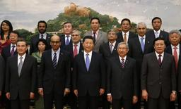 China's President Xi Jinping (front C) poses for photos with guests at the Asian Infrastructure Investment Bank launch ceremony at the Great Hall of the People in Beijing October 24, 2014.  REUTERS/Takaki Yajima