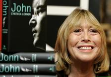 """Cynthia Lennon, first wife of former Beatle John Lennon, poses with copies of her newly published biography entitled """"John""""  at a central London bookshop September 26, 2005. REUTERS/File"""