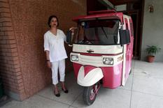 Zar Aslam, president of Pakistan's non-profit Environment Protection Fund, poses beside a Pink Rickshaw in Lahore April 8, 2015. REUTERS/Mohsin Raza
