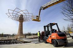 """Workers stand near the 37-meter """"The Tree of Life"""" at the Expo 2015 work site near Milan April 3, 2015. REUTERS/ Giorgio Perottino"""