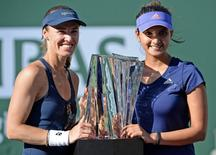 Martina Hingis (SUI) and Sania Mirza (IND) with the championship trophy after winning their doubles final match against Ekaterina Makarova (RUS) and Elena Vesnina (RUS) in the BNP Paribas Open at the Indian Wells Tennis Garden. Mandatory Credit: Jayne Kamin-Oncea-USA TODAY Sports